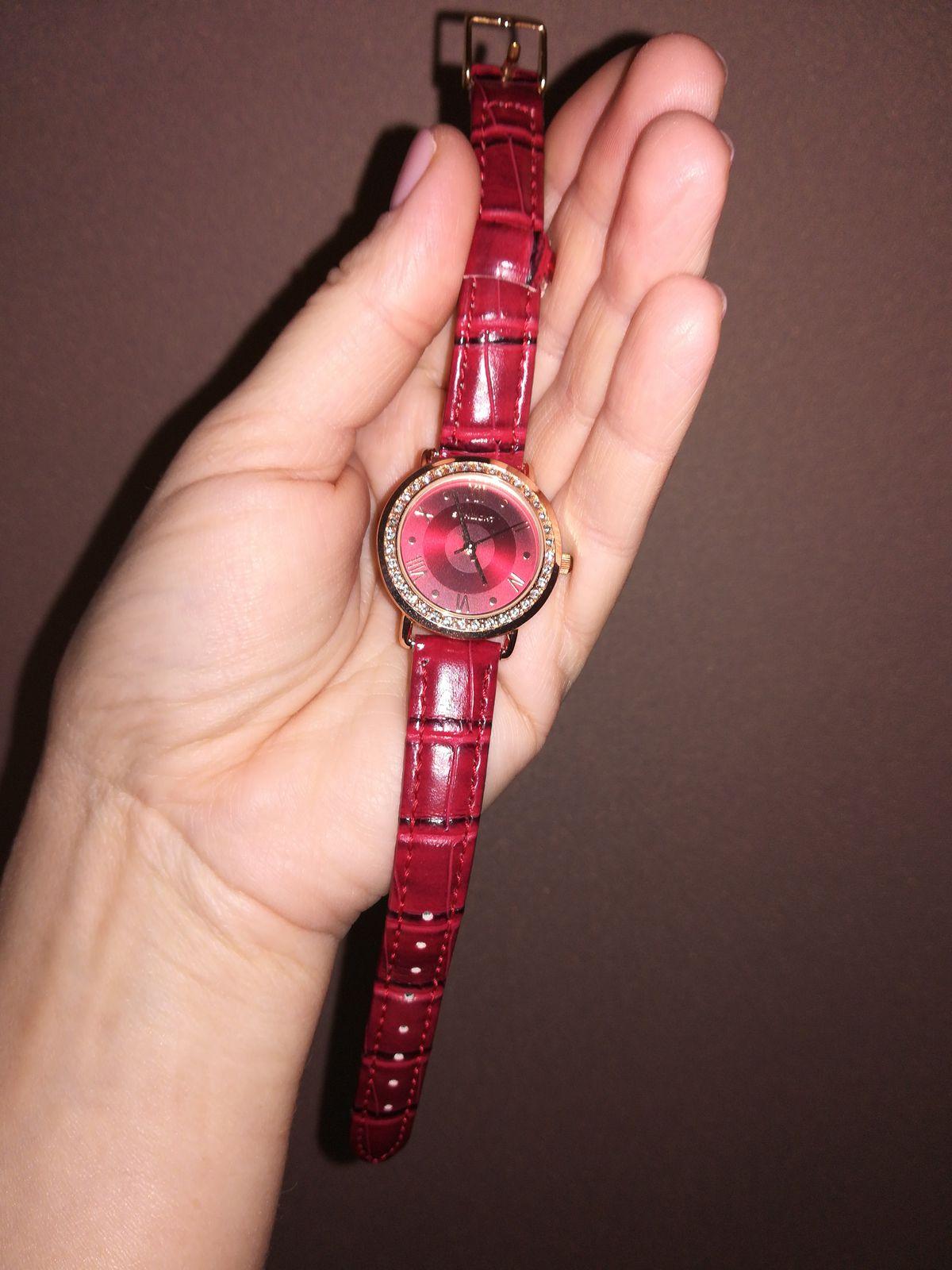 Часы с красным ремешком.